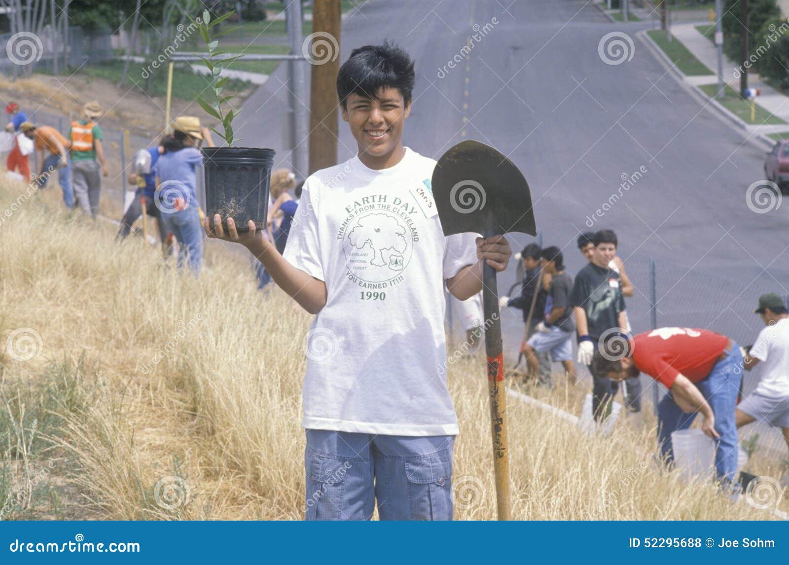 Мальчик нося футболку дня земли участвуя в посадке деревьев чистыми & зелеными волонтерами Лос-Анджелеса Conservatio