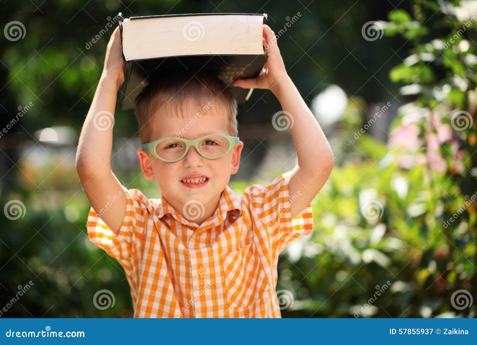 Мальчик портрета счастливый держа большую книгу на его первый день к школе или питомнику Outdoors, назад к концепции школы