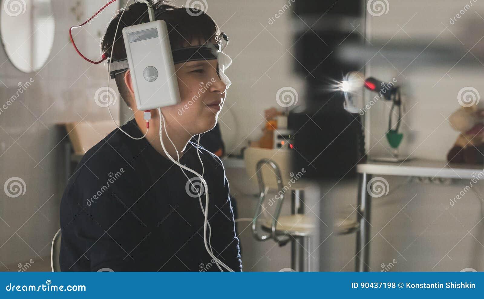 Мальчик подростка с электродами на голове смотря к монитору - диагностике ` s детей здравоохранения - офтальмология