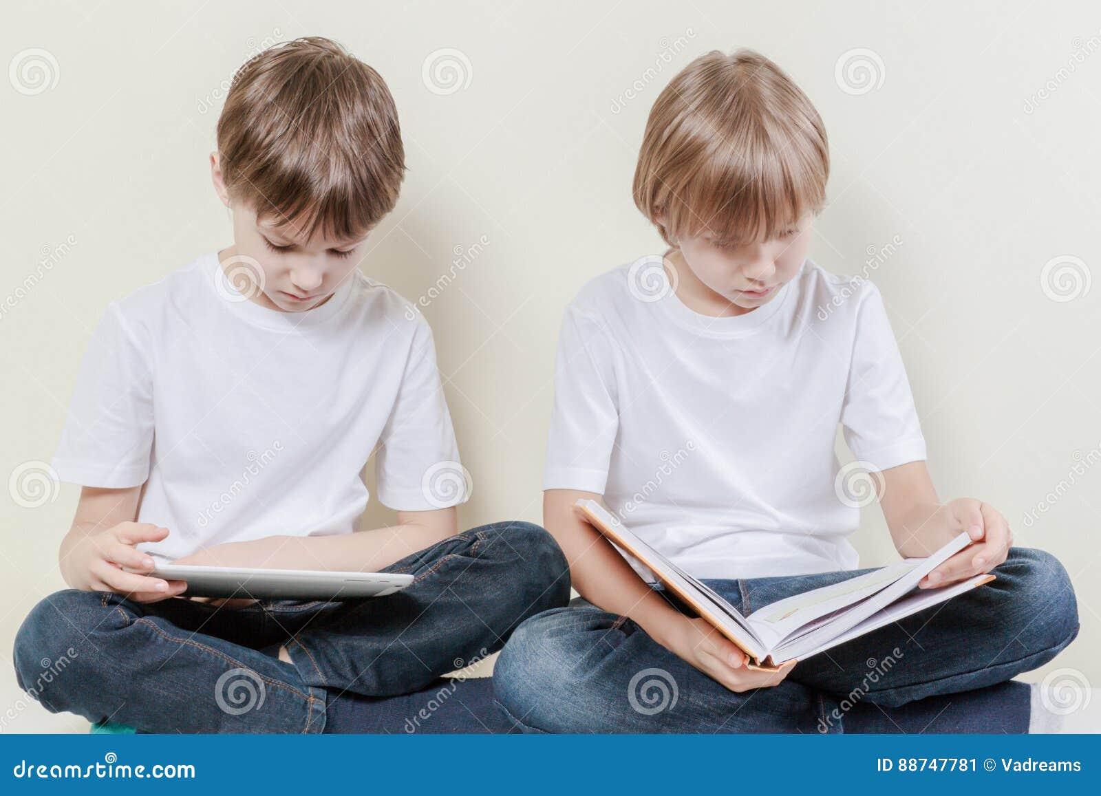 Мальчик при планшет и ребенк читая книгу Ягнит концепция отдыха образования