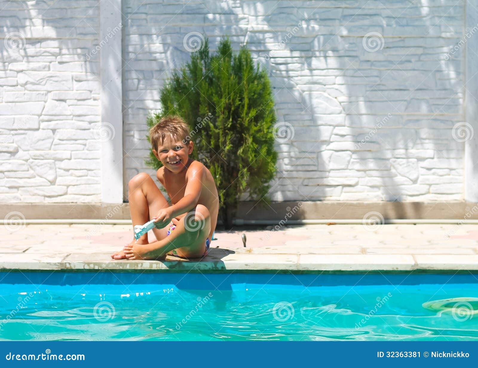 Мальчик сидит около бассейна