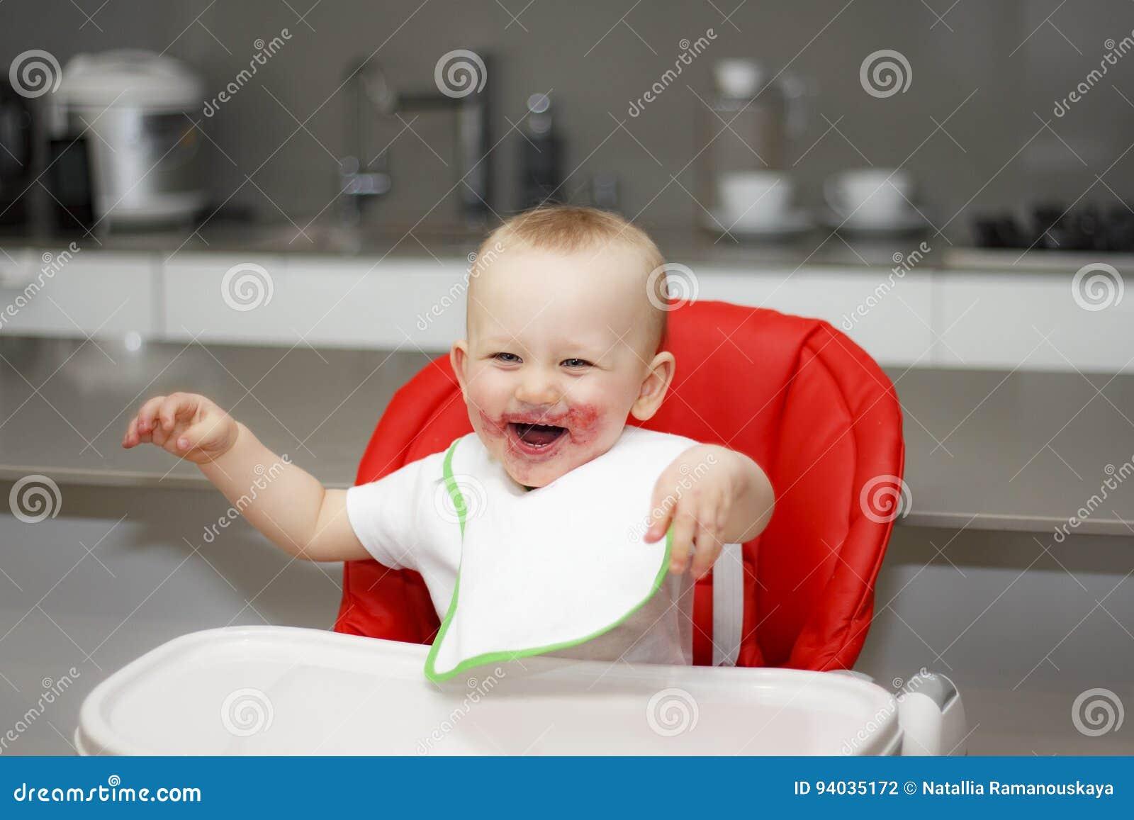 Мальчик сидя в высоком стуле и смеяться над