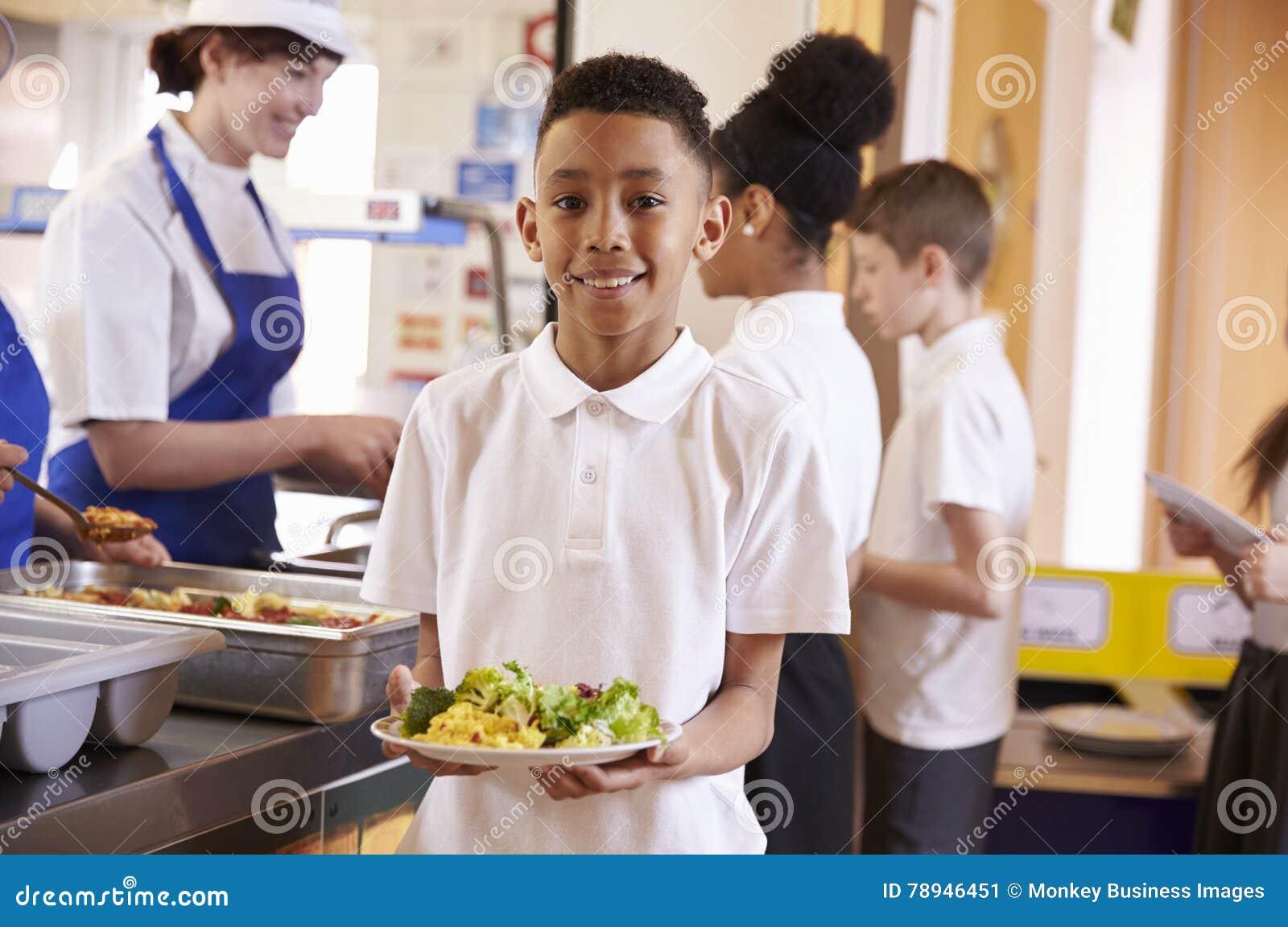 Мальчик смешанной гонки держа плиту еды в школьном кафетерии