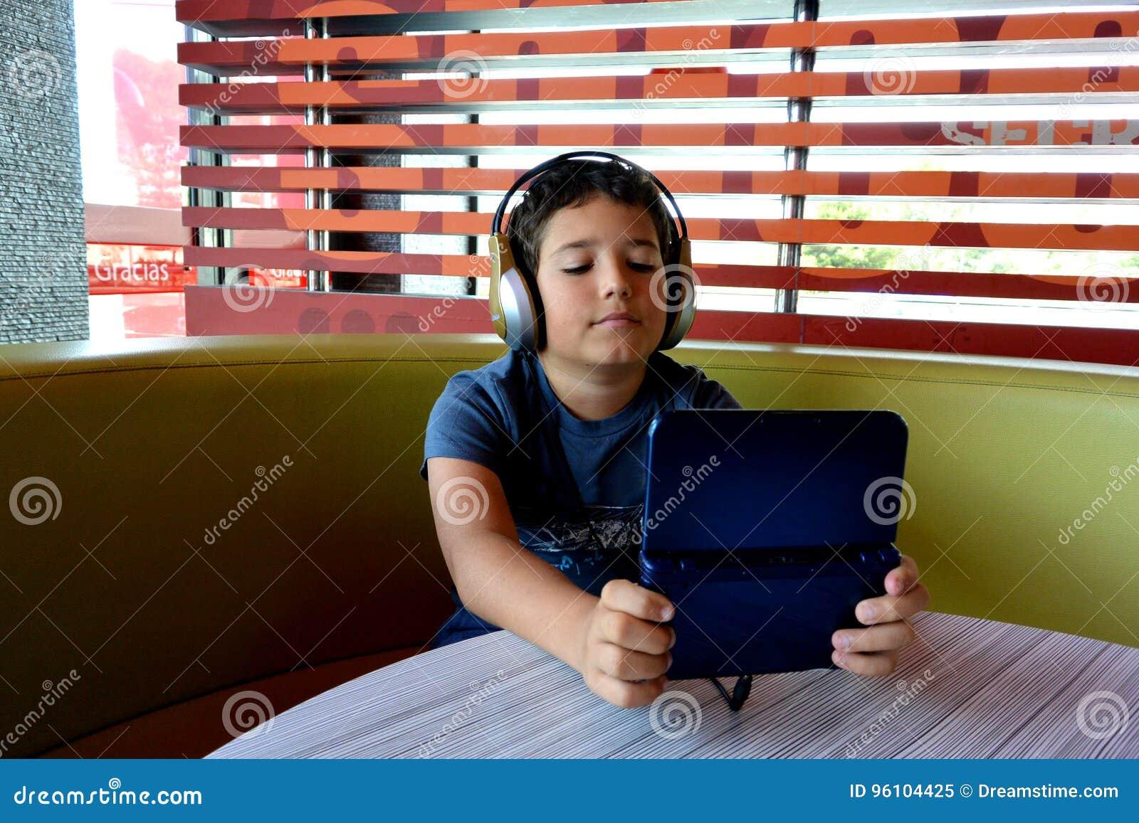Мальчик с наушниками играет с электронной игрой
