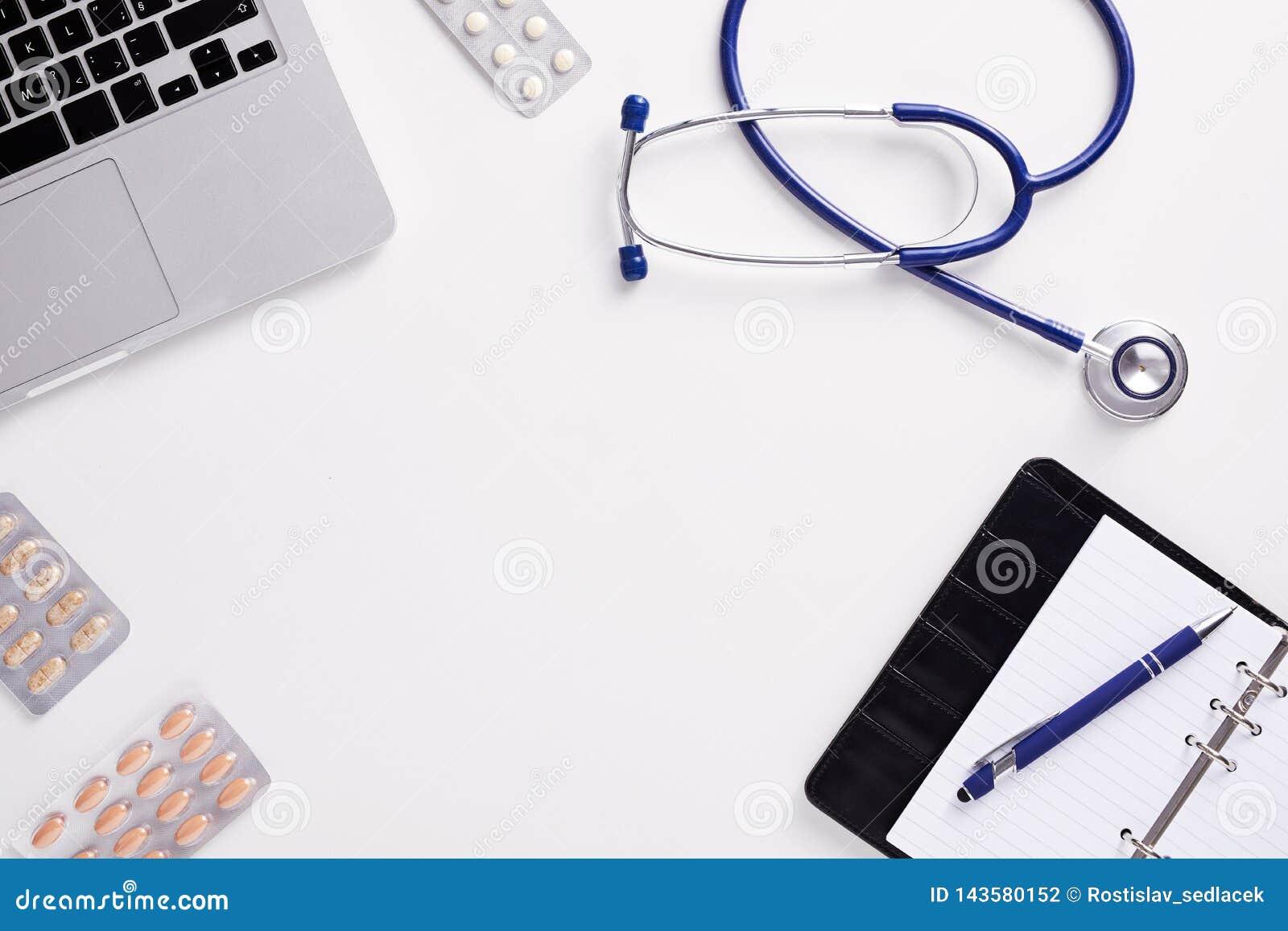 Медицинский стол со стетоскопом, latptop, таблетками и чистым листом бумаги на доске сзажимом для бумаги