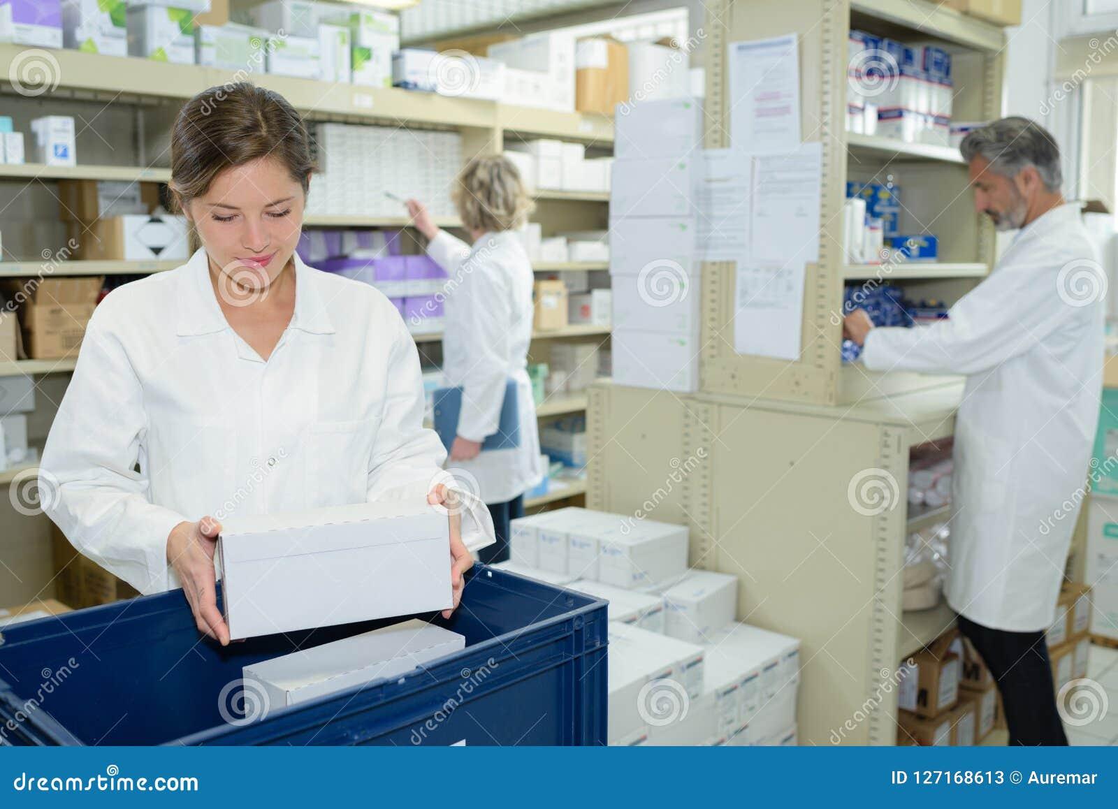 Медсестра и аптекари работая в фармации
