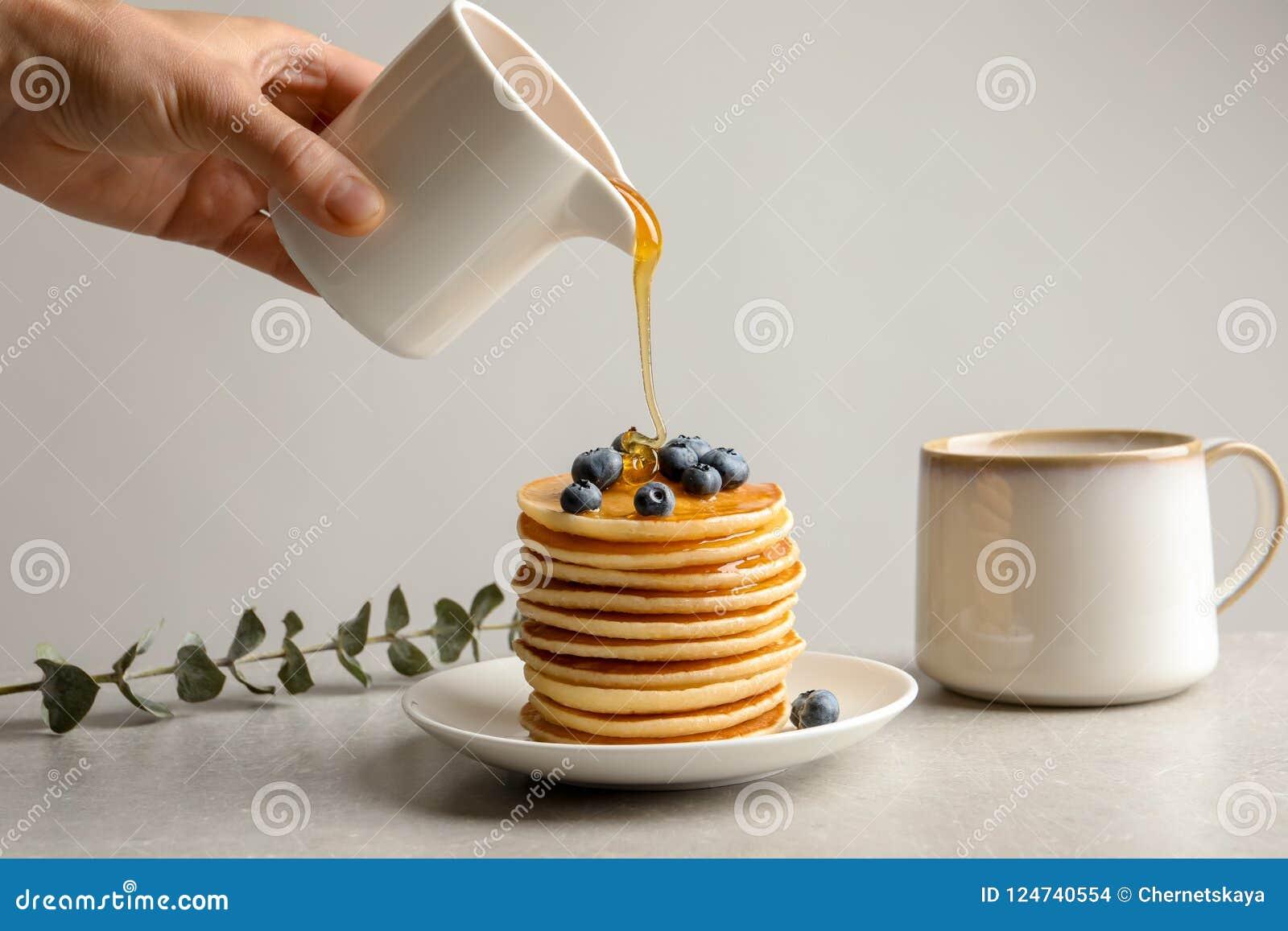 Мед женщины лить на вкусные блинчики с ягодами