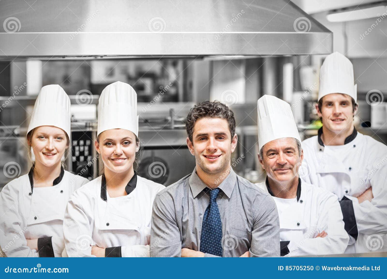 Менеджер с портретом шеф-поваров в профессиональной кухне