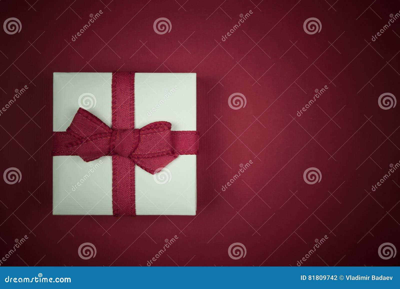 Меньший белый подарок изолированный на красной предпосылке