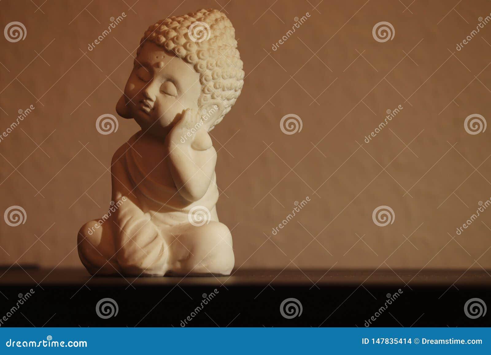 Меньший Будда спать мирно в сидя положении