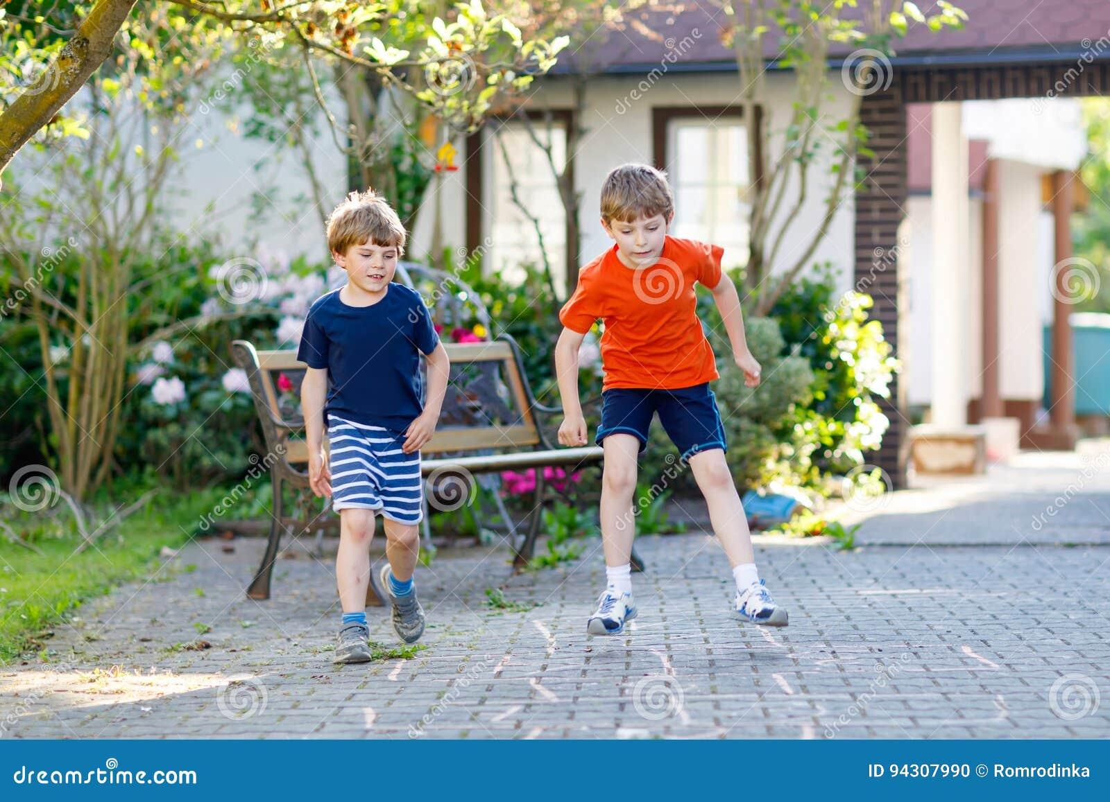 2 меньших мальчика детей школы и preschool играя классики на спортивной площадке
