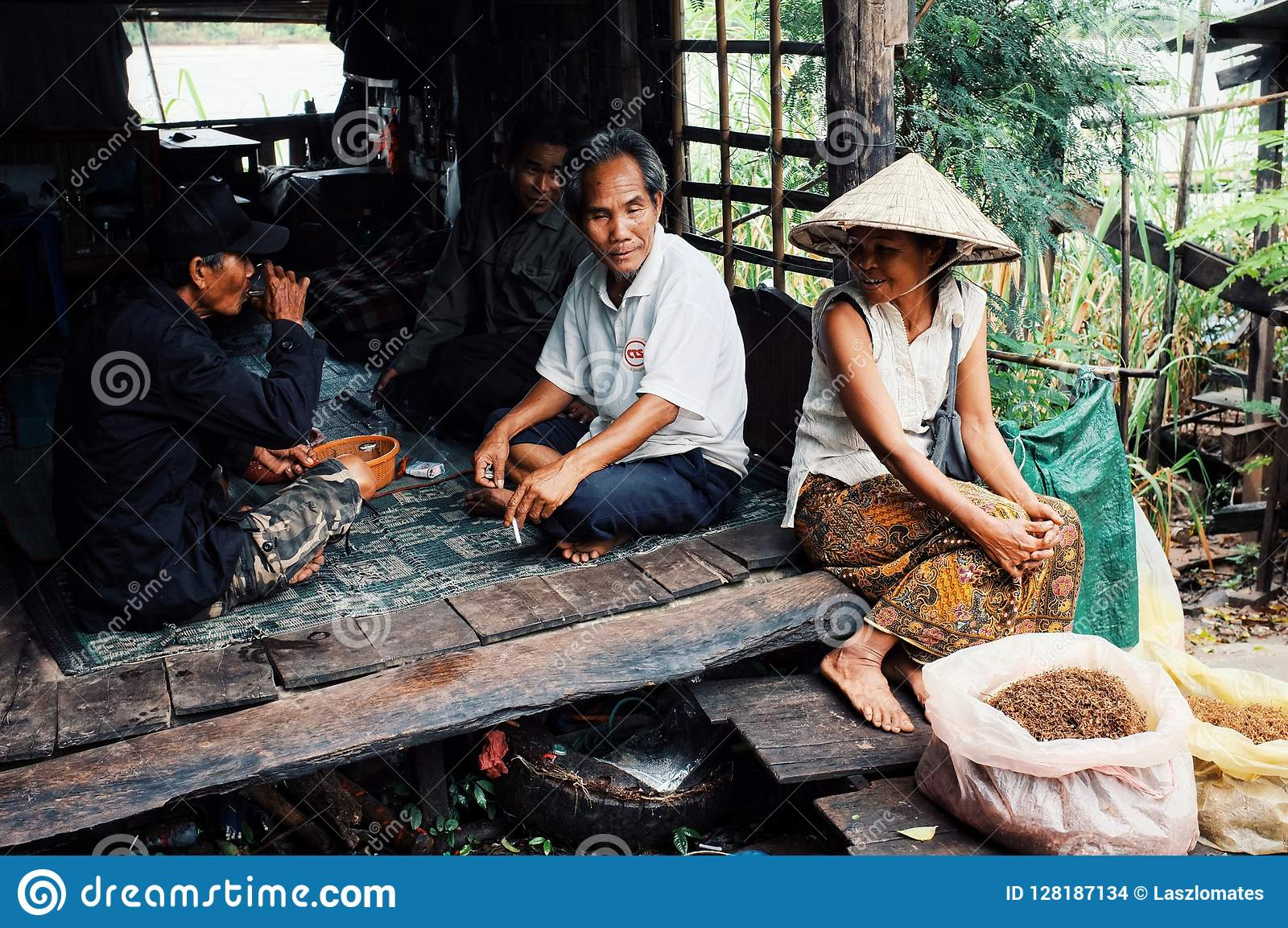 местная женщина в традиционной конической шляпе продавая табак на рынке деревни рядом с Меконгом с ее сидеть семьи