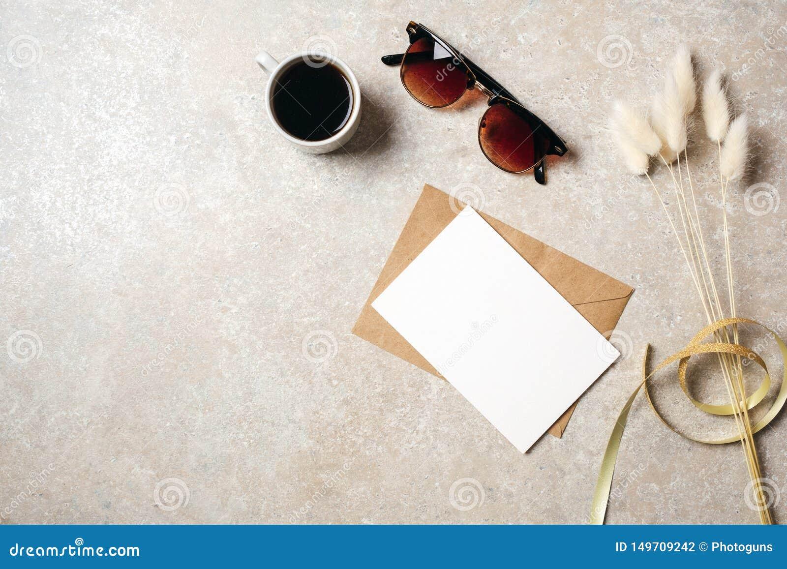 Место для работы стола домашнего офиса хипстера с солнечными очками, карта чистого листа бумаги и конверт kraft, сухой цветок с л