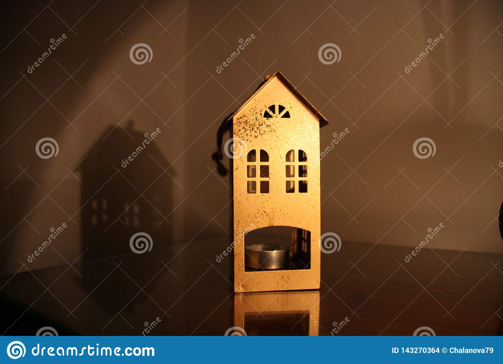Металлический подсвечник в форме дома на таблице в темном вечере со светом лампы