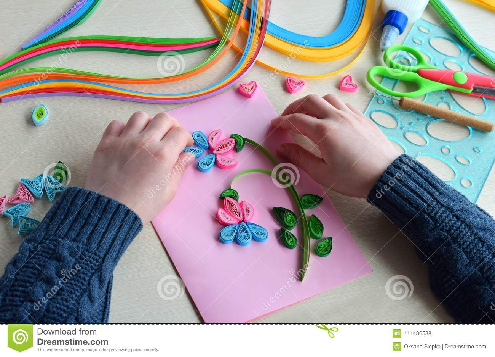 Метод Quilling Мальчик делая украшения или поздравительную открытку Бумажные прокладки, цветок, ножницы Handmade ремесла на празд