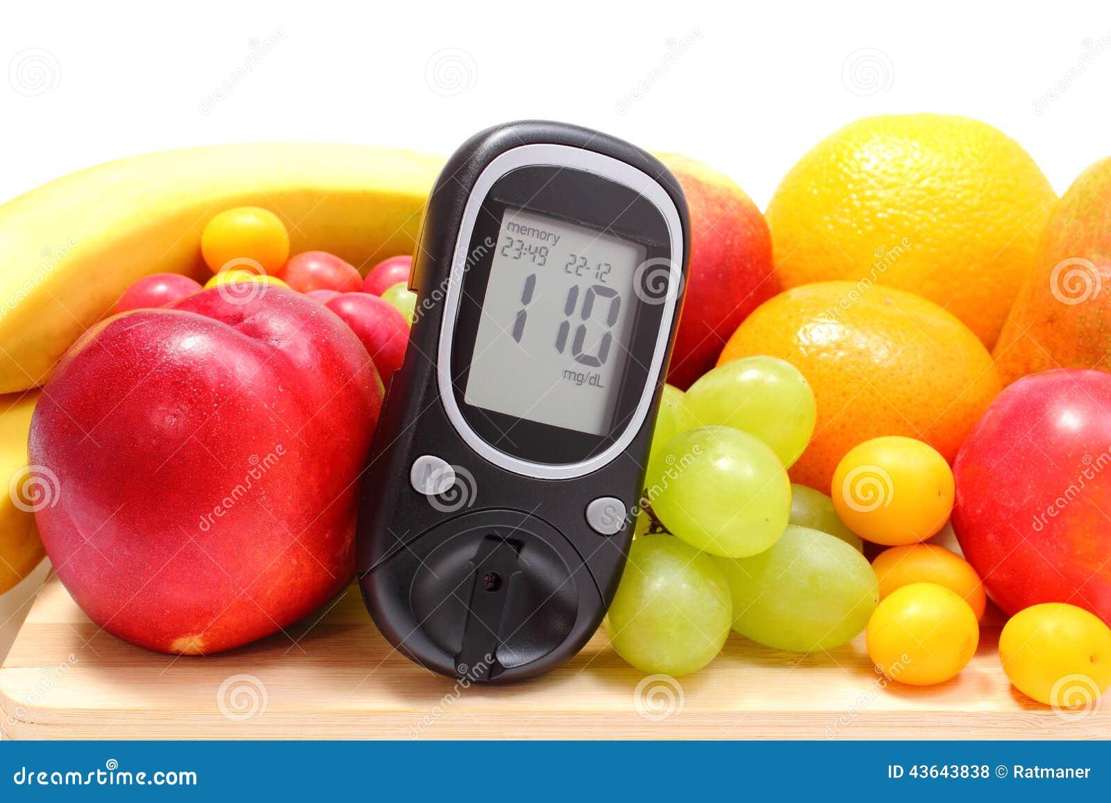 Метр глюкозы и свежие фрукты на деревянной разделочной доске
