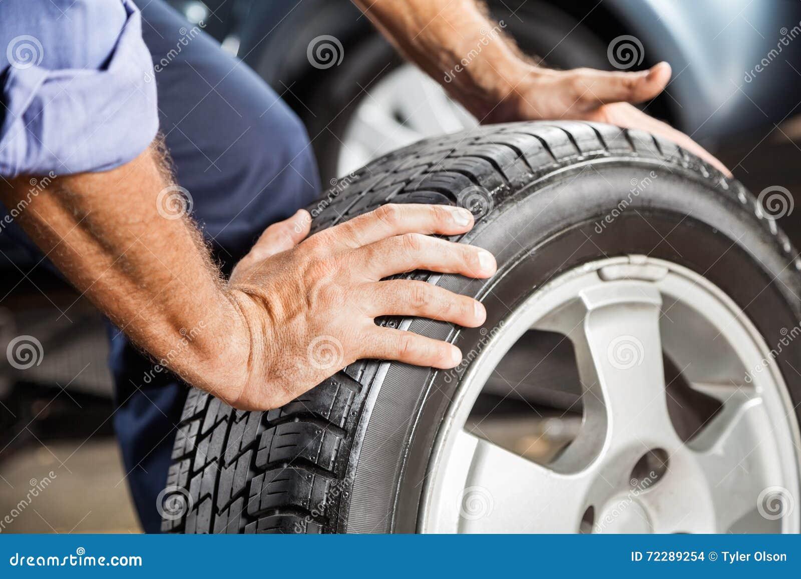 Download Механик держа автошину автомобиля на гараже Стоковое Фото - изображение насчитывающей резина, сплавам: 72289254