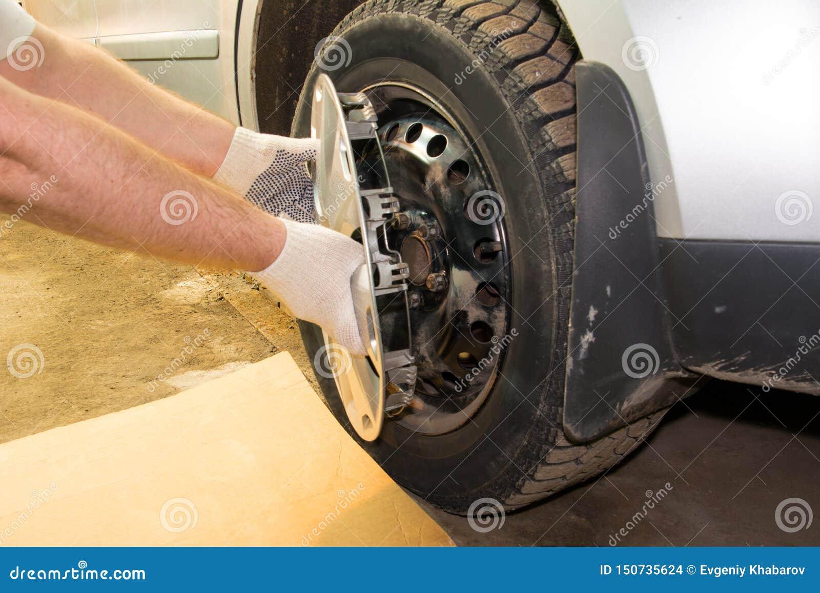 Механик извлекая колпак из колеса автомобиля
