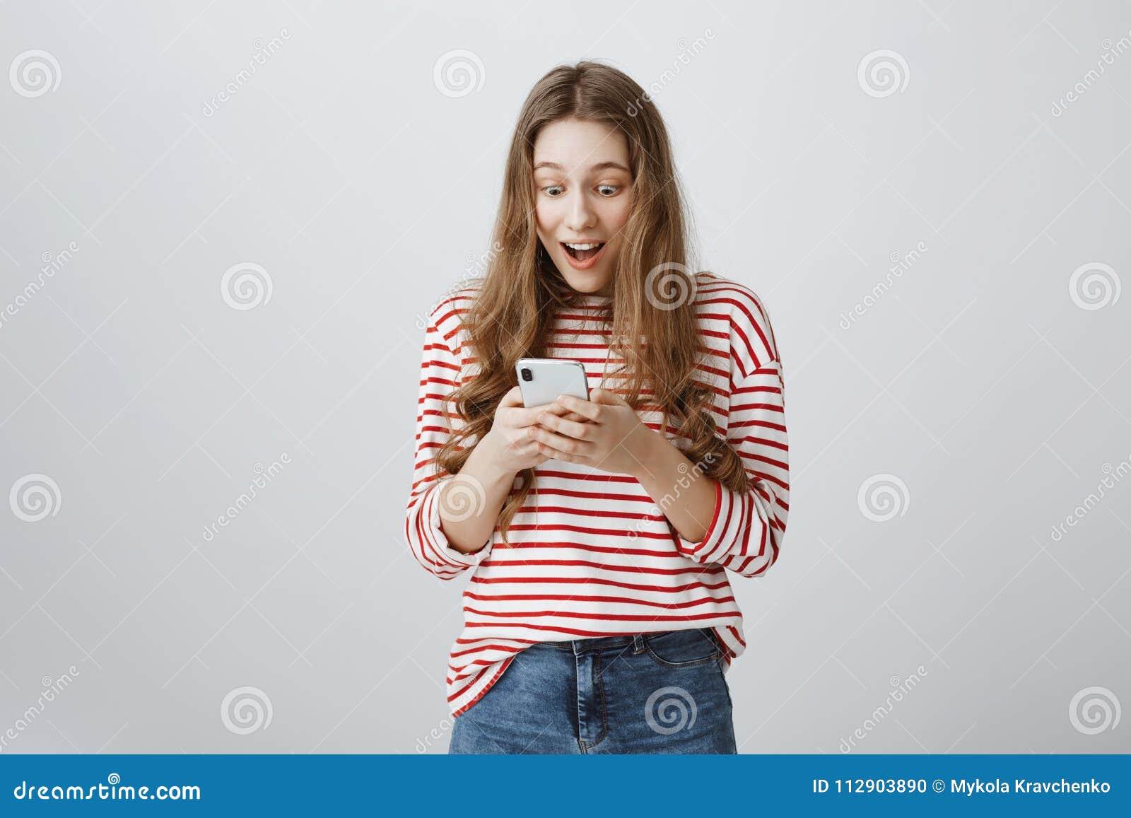 Мечты приходят верно с помощью технологии Портрет ультрамодной современной женщины при длинные светлые волосы держа smartphone, с