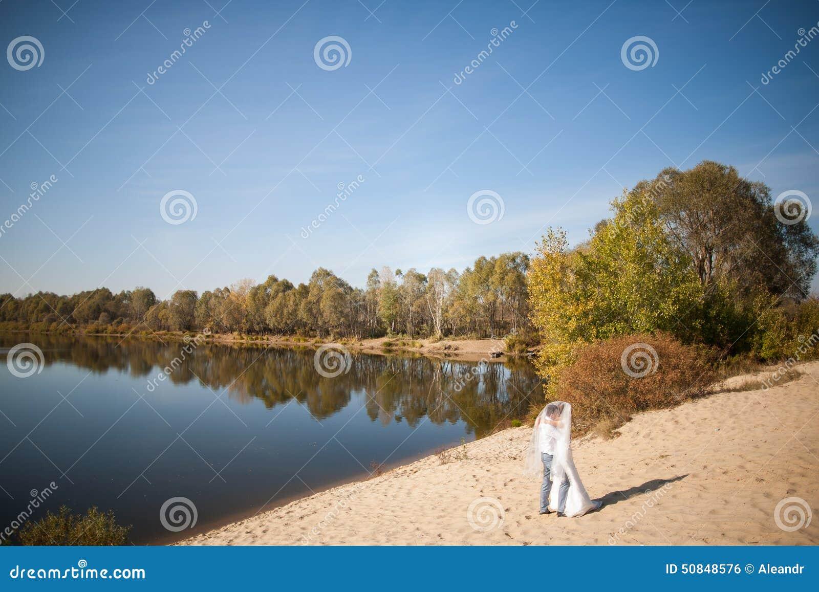 Медовый месяц как раз пожененных wedding пар счастливая невеста, groom стоя на пляже, целующ, усмехающся, смеющся над, имеющ поте