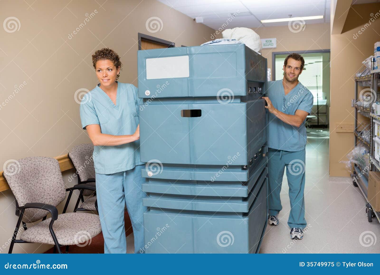 Медсестра нажимая вагонетку пока помощь коллеги