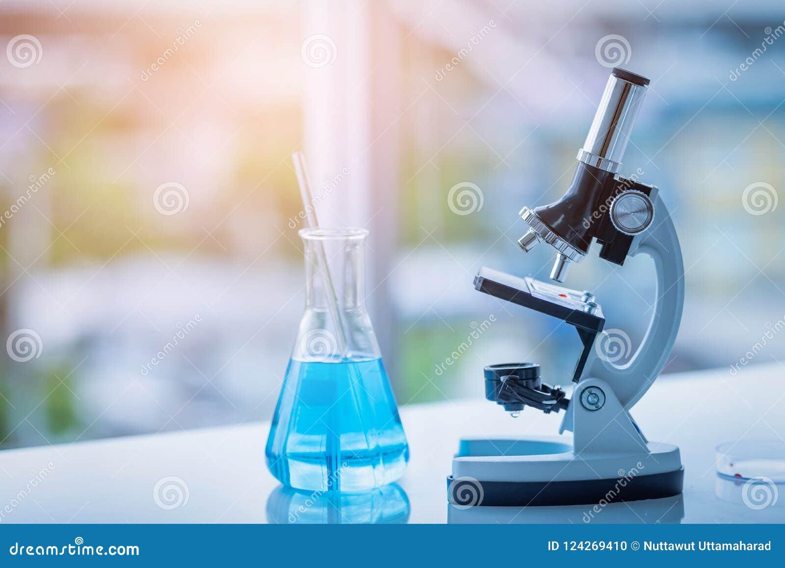 Микроскоп и Beaker на таблице в лаборатории Химия науки