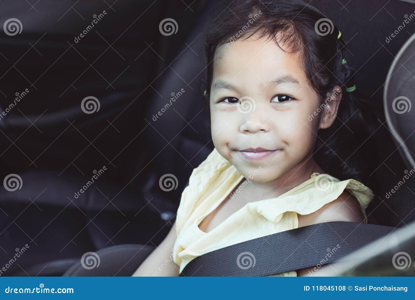 Милая азиатская девушка маленького ребенка сидя в автокресле