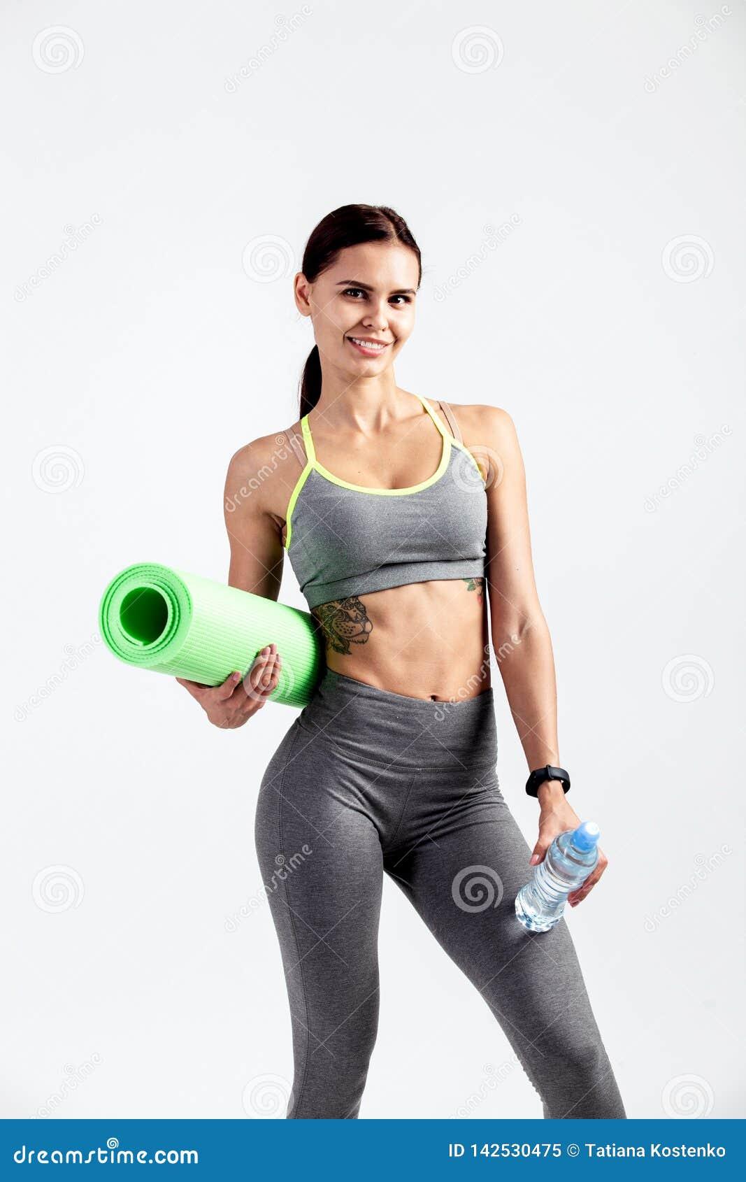 Милая атлетическая девушка одетая в сером sportswear стоит с циновкой фитнеса и бутылкой воды в ее руках на