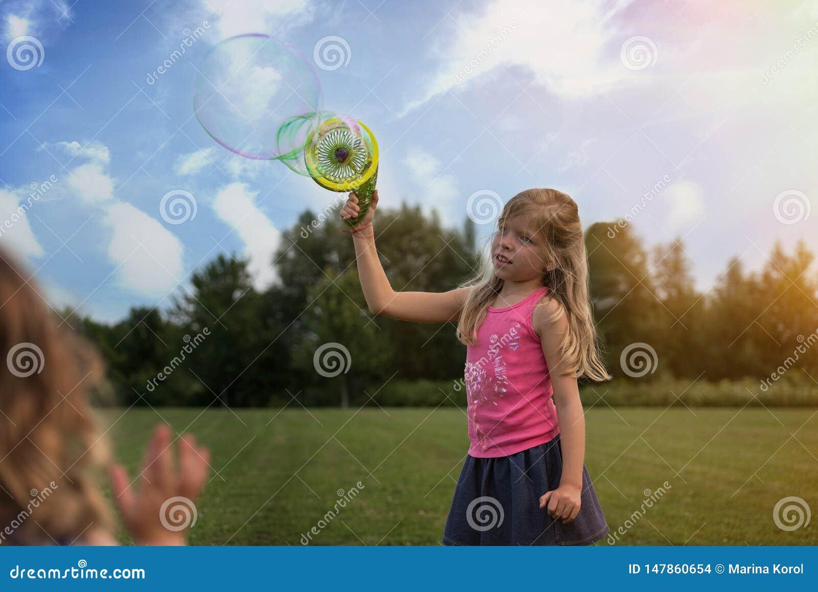 Милая белокурая кавказская девушка делает пузыри на поле