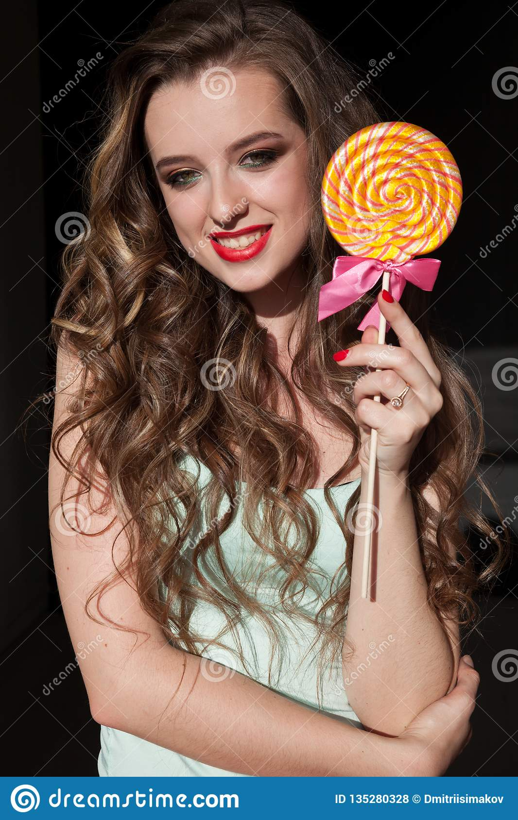 Милая девушка ест конфету леденца на палочке конфеты сладкую