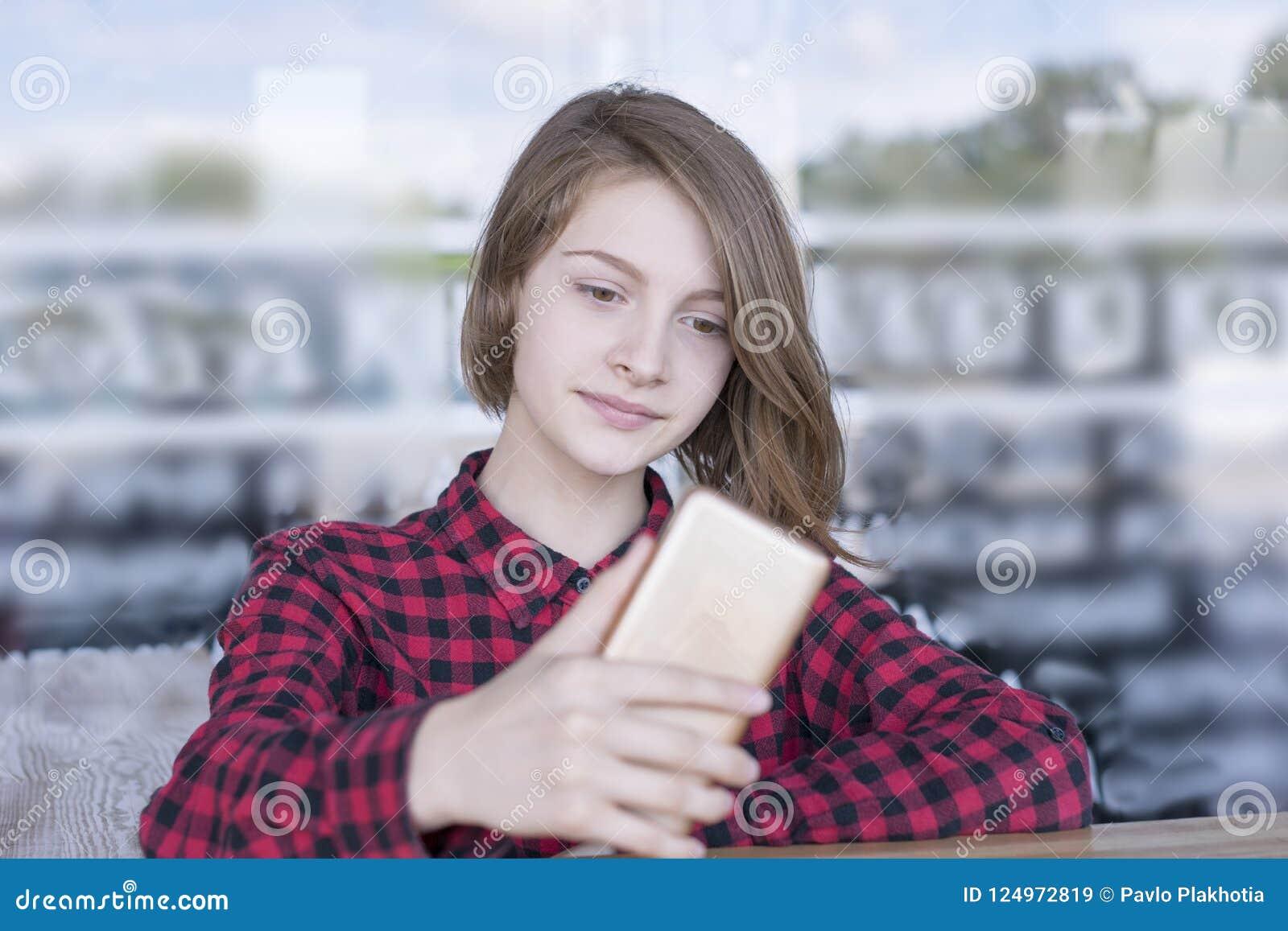 Милая девушка используя телефон outdoors