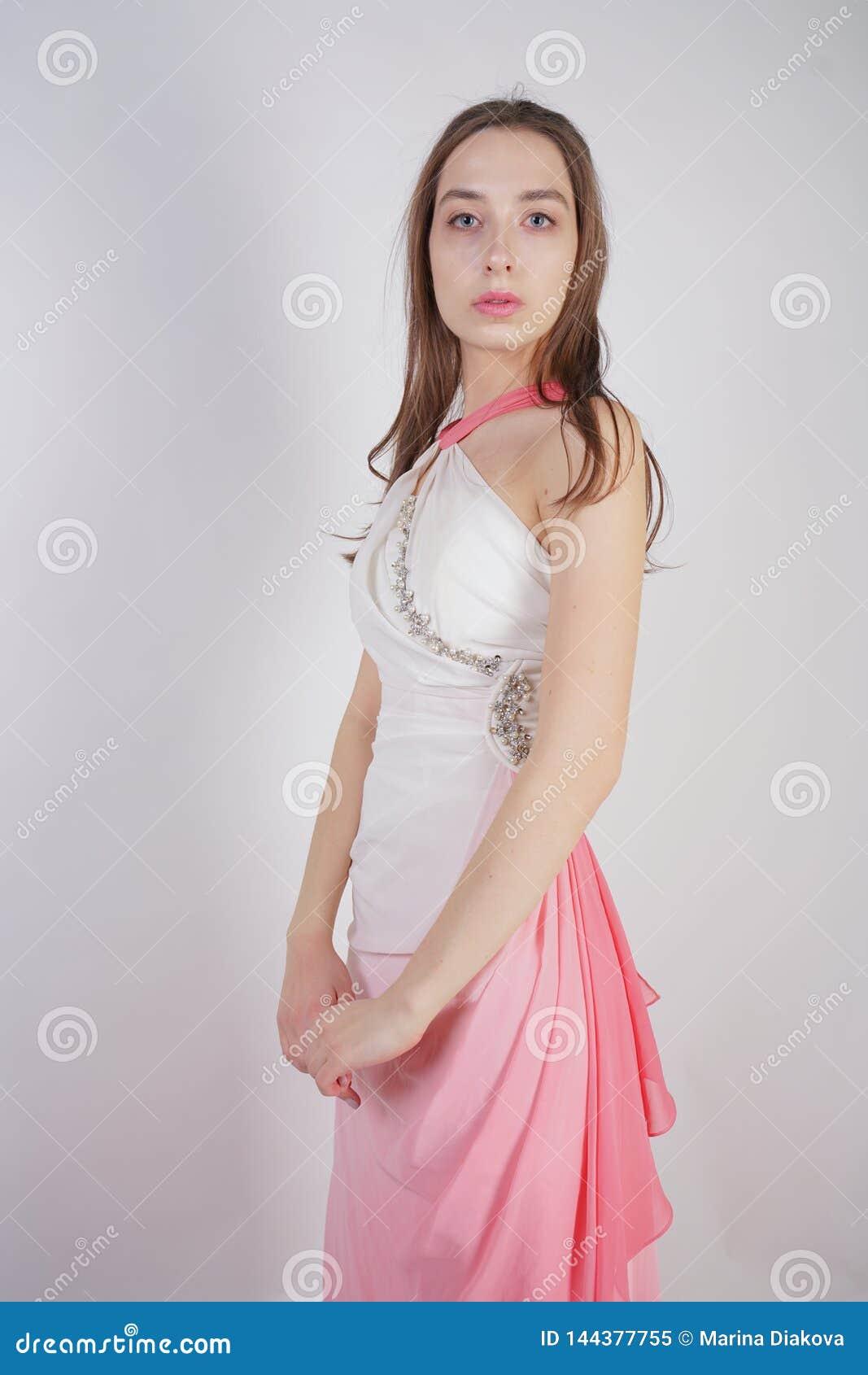 Милая девушка подростка стоит в платье лета с розовым Ombre на белой предпосылке в студии
