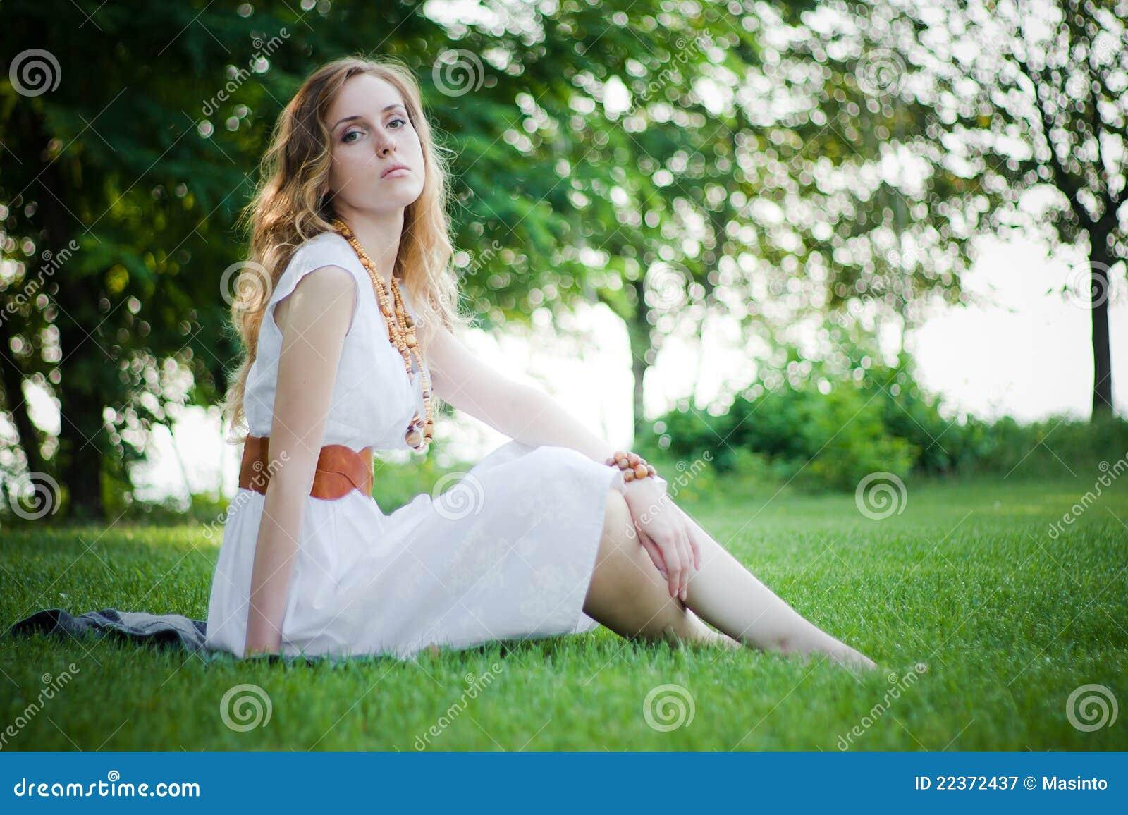 Милая девушка сидит на траве