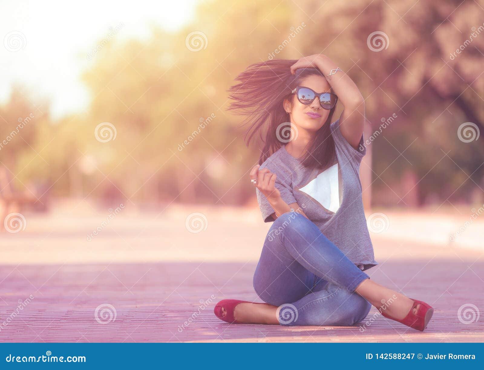 Милая девушка сидя на поле с двигая волосами