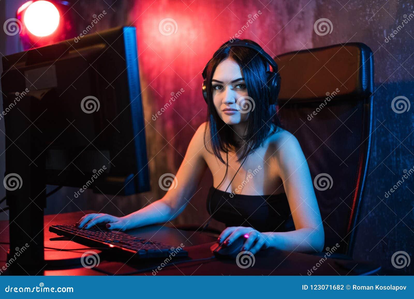 Милая женская девушка gamer сидит в уютной комнате за компьютером и играет игры Видео в реальном маштабе времени компьютера женщи