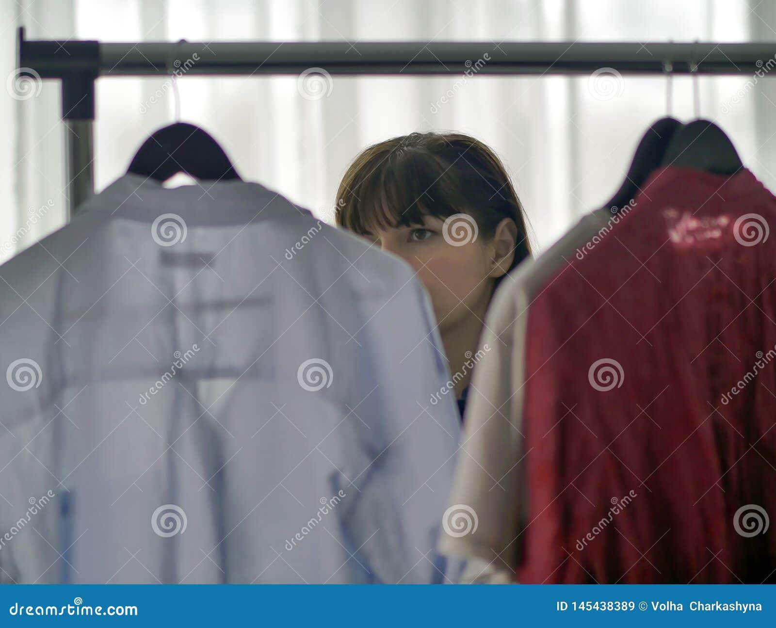 Милая женщина брюнета рассматривая одежды на вешалках