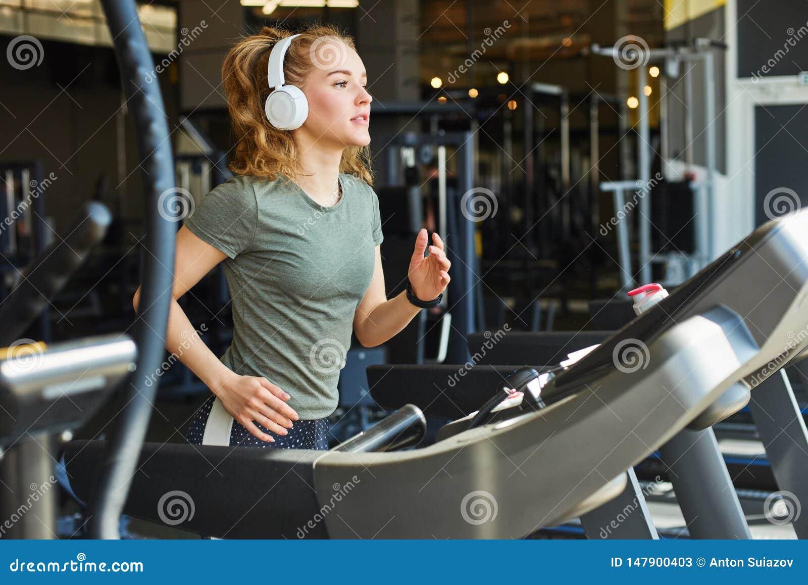 Милая женщина jogging в спортзале