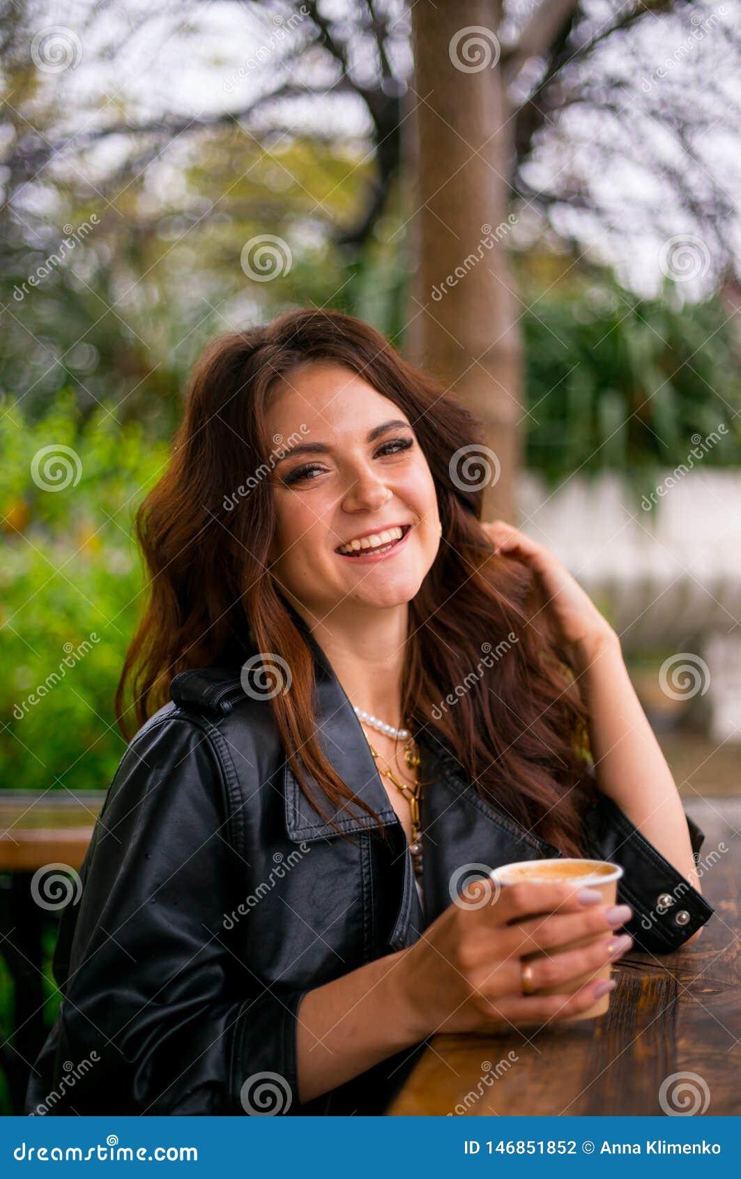Милая жизнерадостная молодая женщина в куртке lether сидит на кофе террасы кафа выпивая от бумажного стаканчика Кофе, который нуж