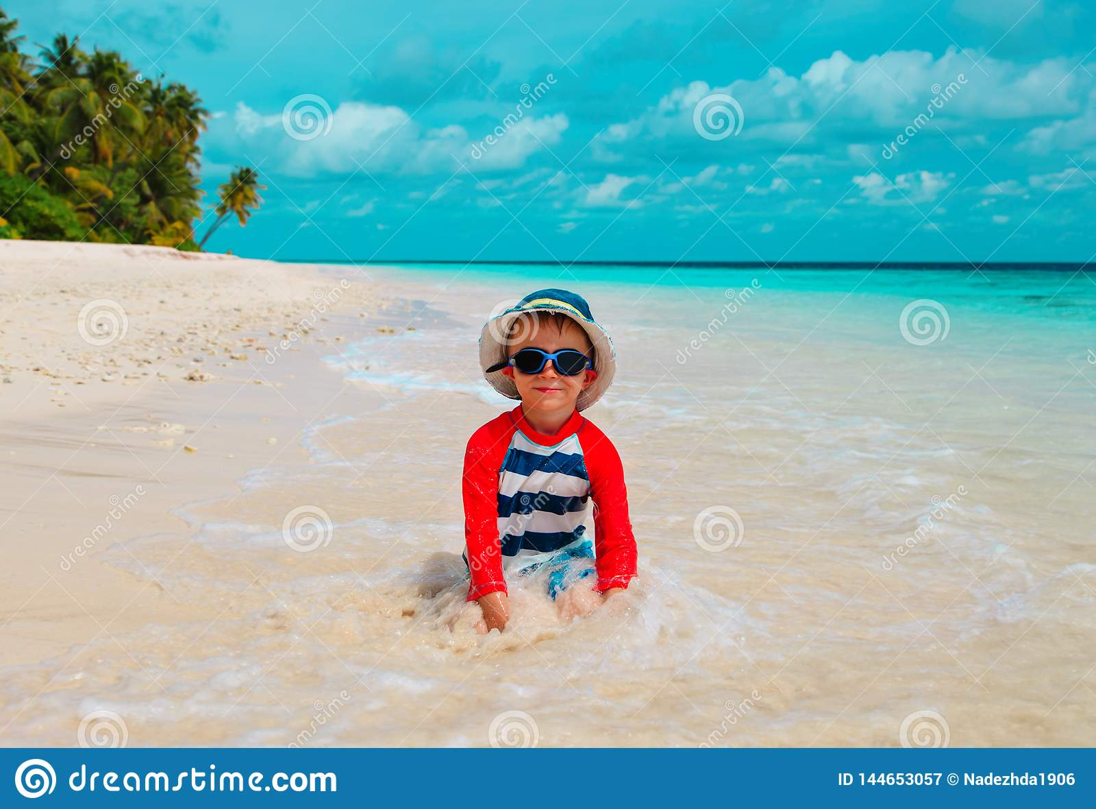 Милая игра мальчика с водой и песком на пляже