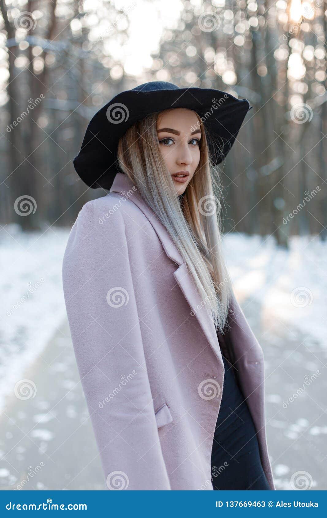 Милая красивая молодая женщина в стильных одеждах очарования зимы идет в шикарную шляпу в снежном лесе на день зимы солнечный