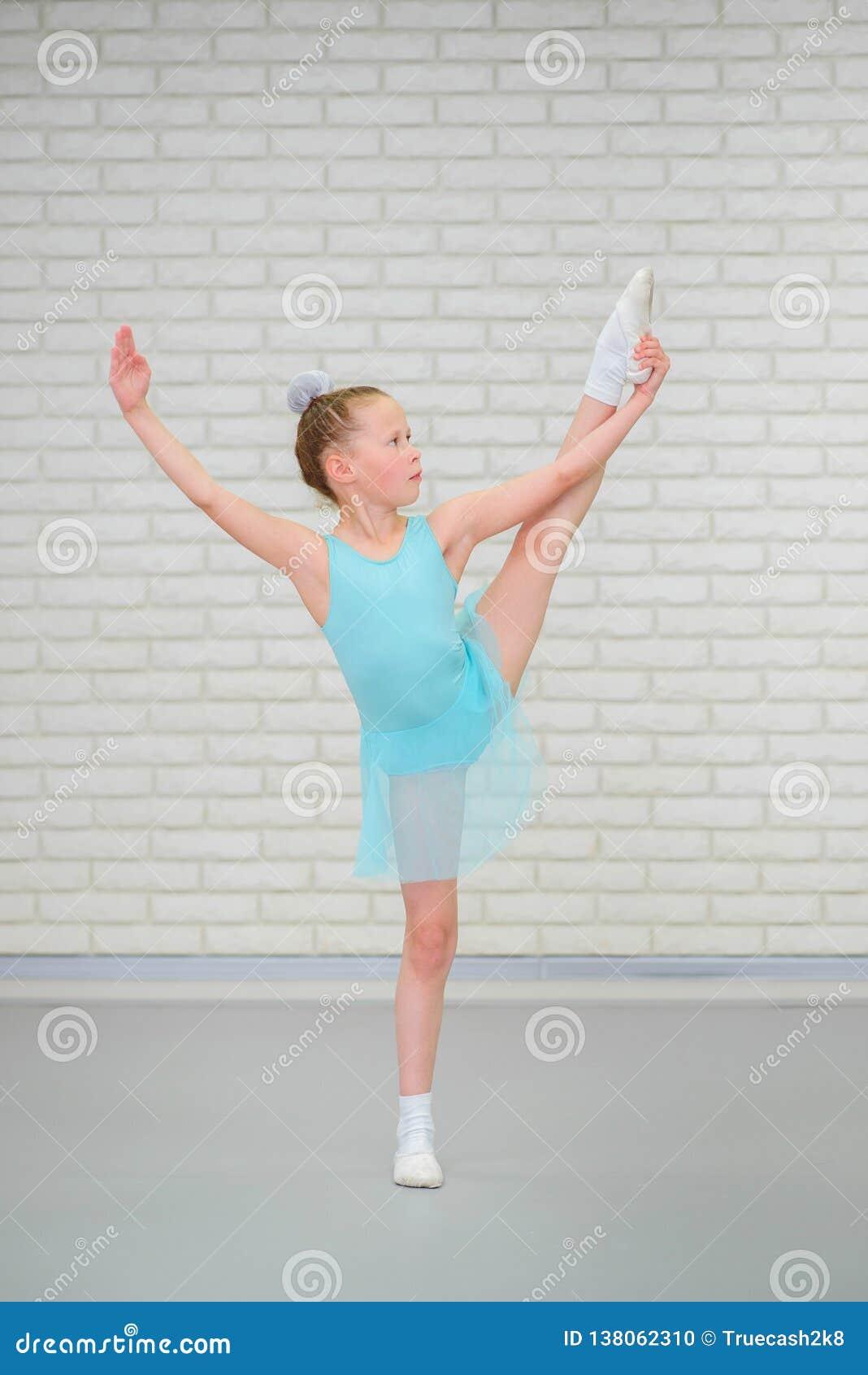 Милая маленькая балерина в голубых танцах платья на классе балета