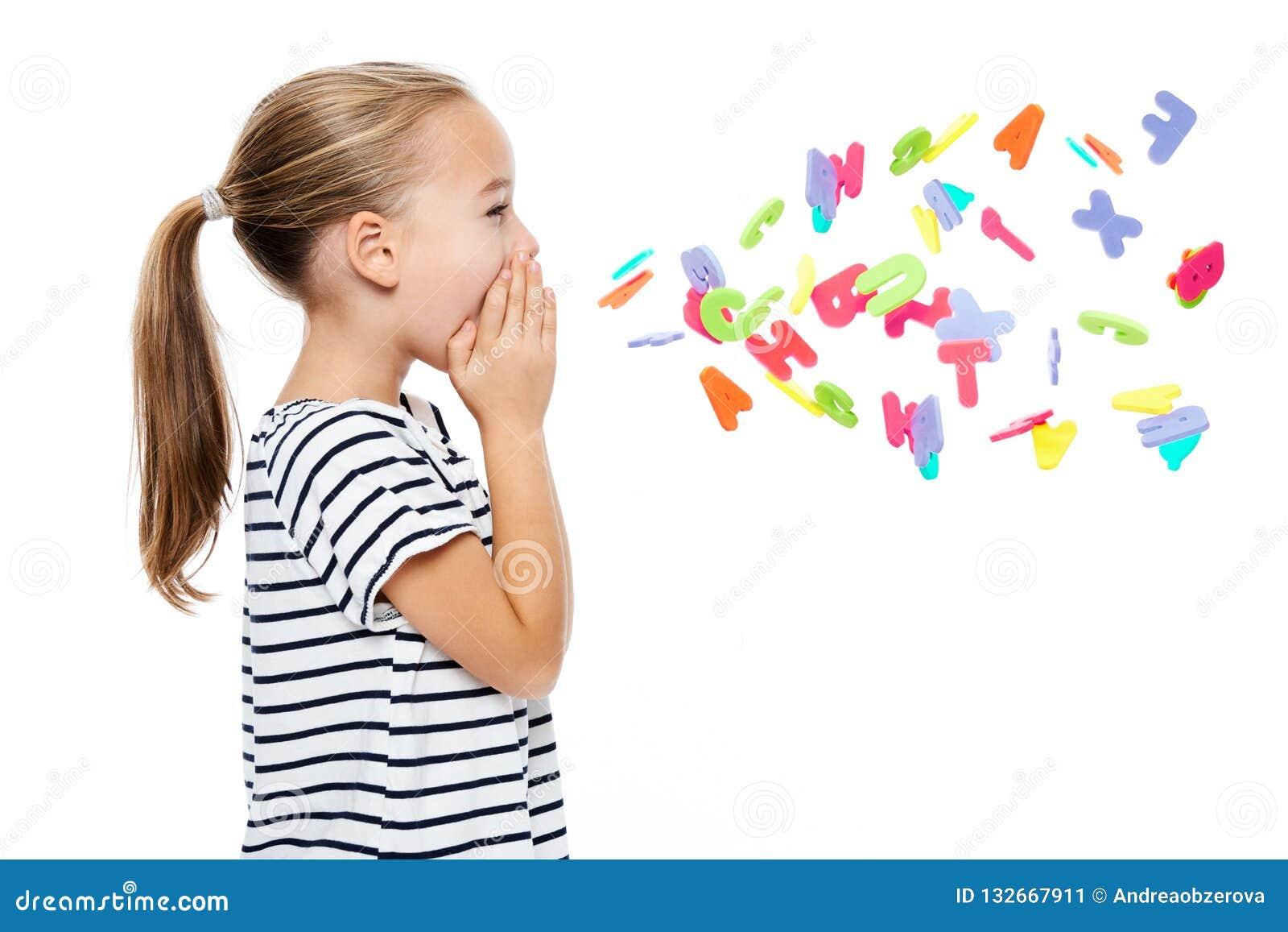 Милая маленькая девочка в обнажанной футболке крича вне письма алфавита Концепция логопедии над белой предпосылкой
