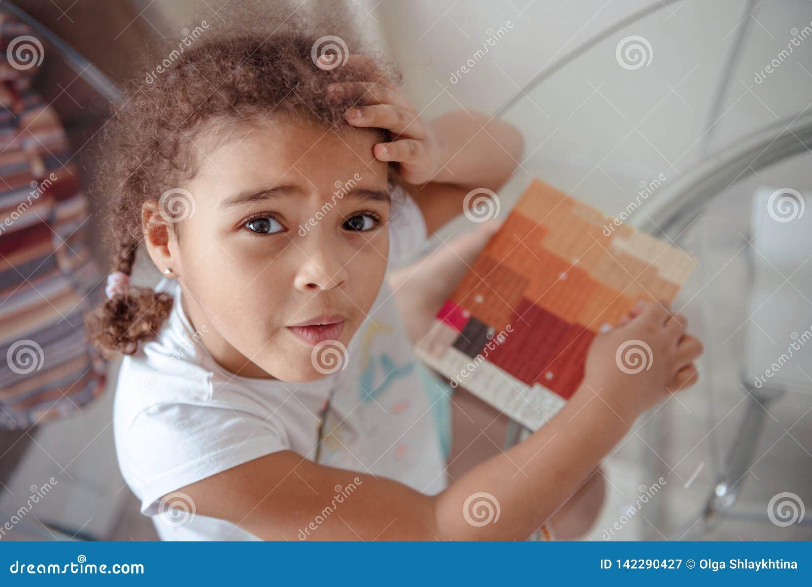 Милая маленькая девочка делает applique, клеит красочный дом, прикладывая бумагу цвета используя ручку клея пока делающ искусства