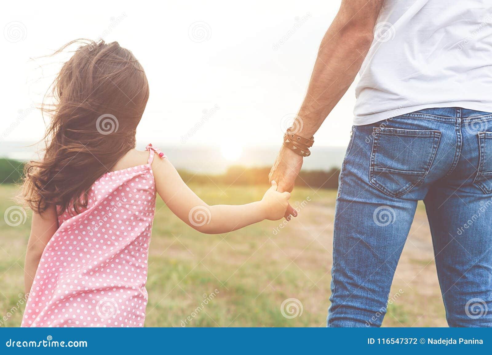 Милая маленькая девочка держа руку ` s отца