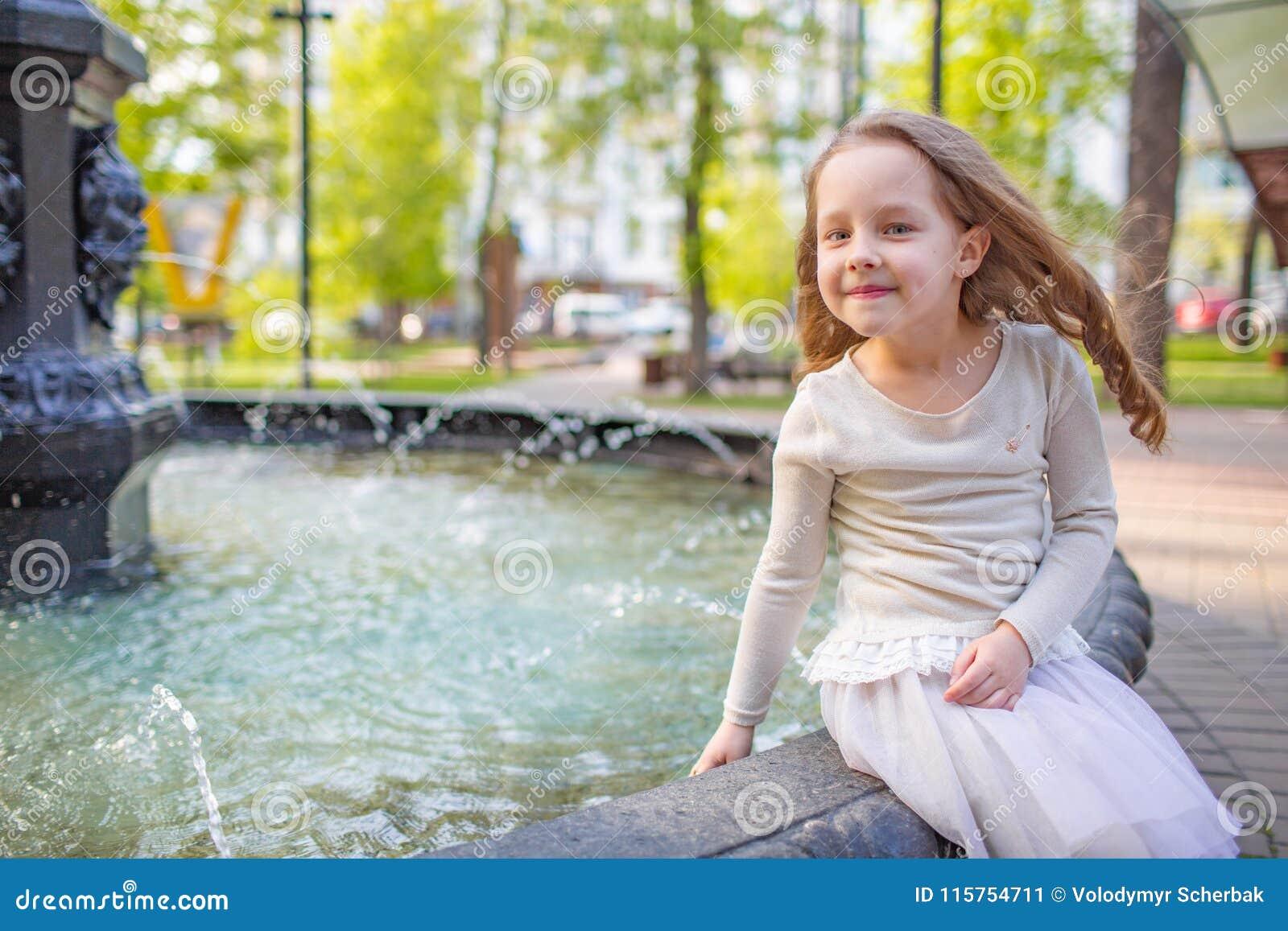 Милая маленькая девочка играя фонтаном города на горячий и солнечный летний день Ребенок имея потеху с водой в лете Активный отды