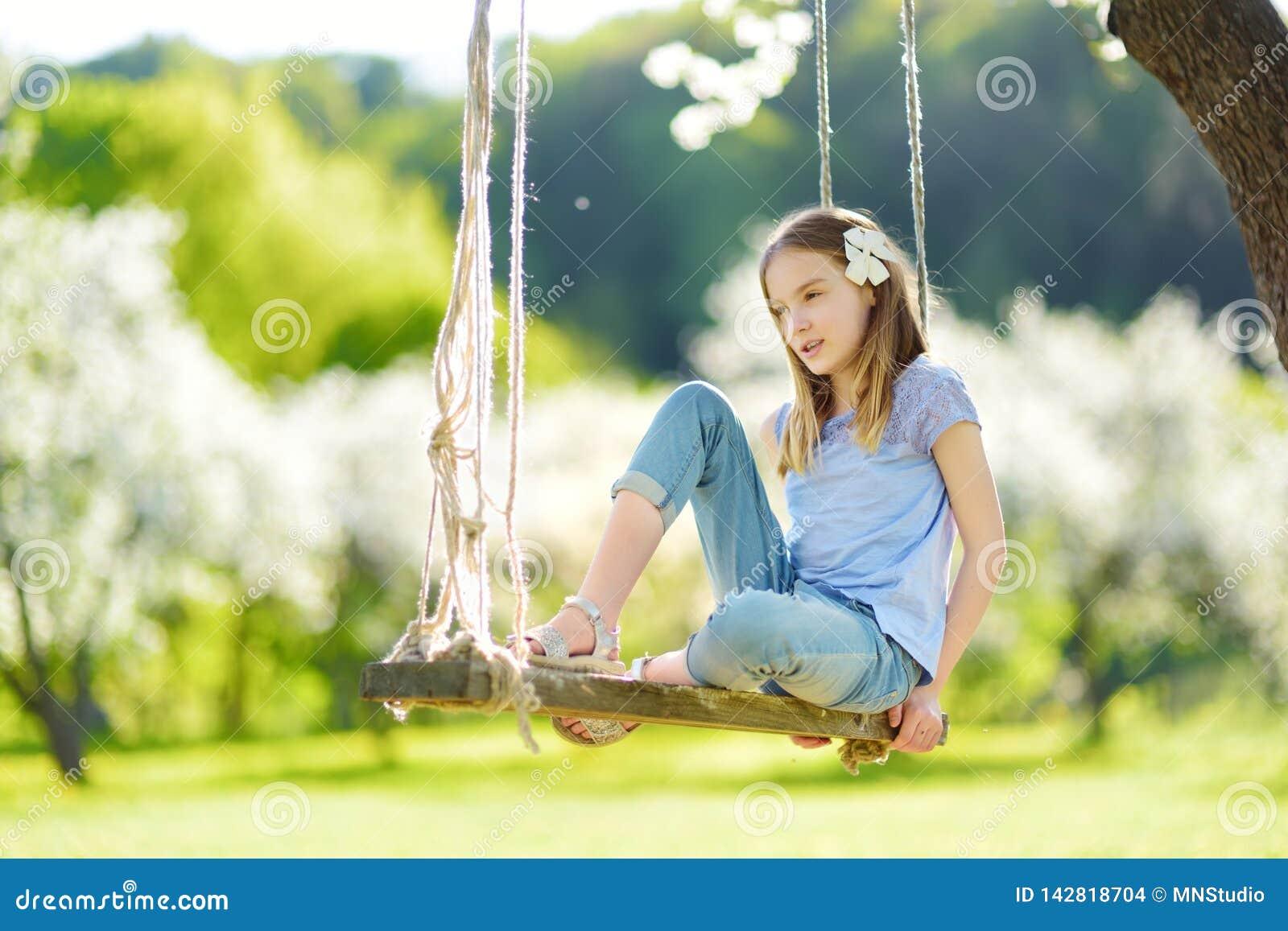 Милая маленькая девочка имея потеху на качании в blossoming старом саде яблони outdoors на солнечный весенний день