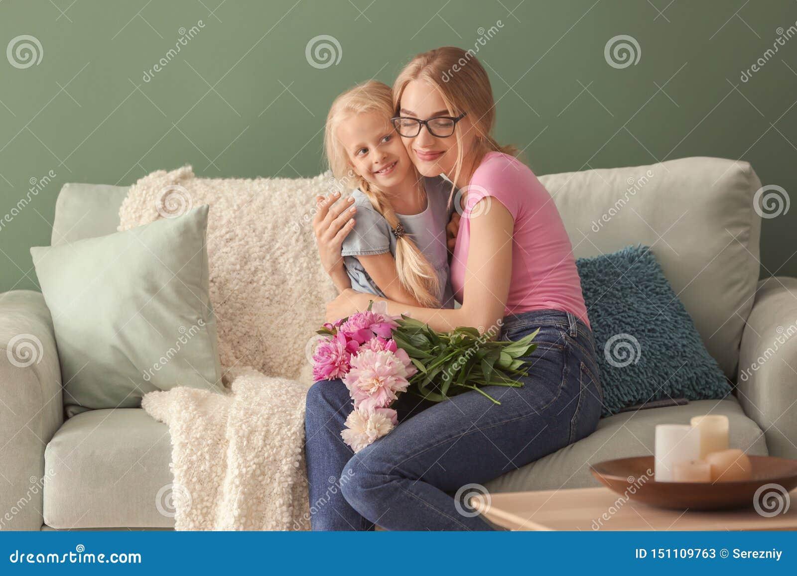 Милая маленькая девочка и ее мать с красивыми цветками сидя на софе дома