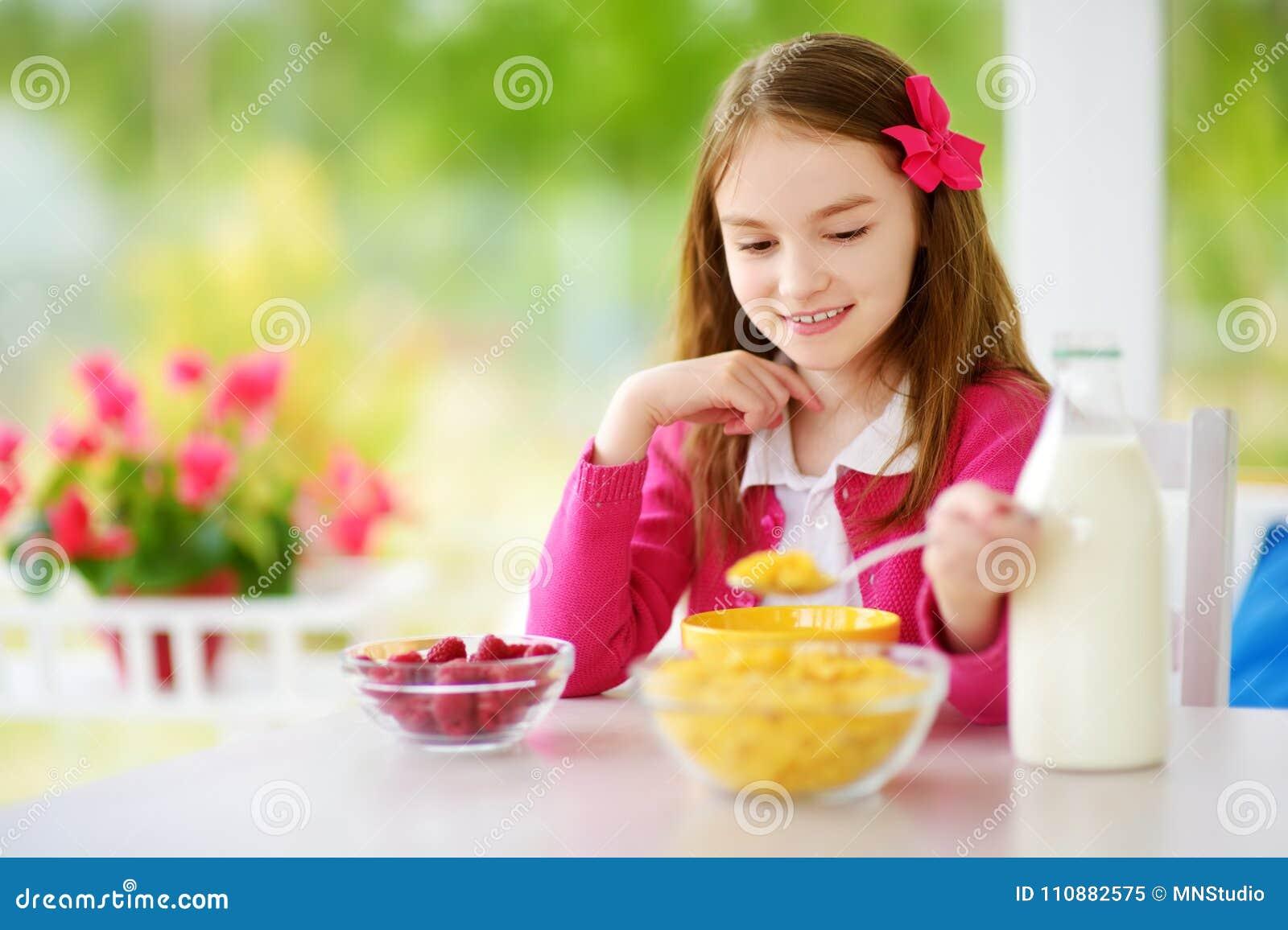 Милая маленькая девочка наслаждаясь ее завтраком дома Милый ребенок есть хлопья мозоли и поленики и питьевое молоко перед школой