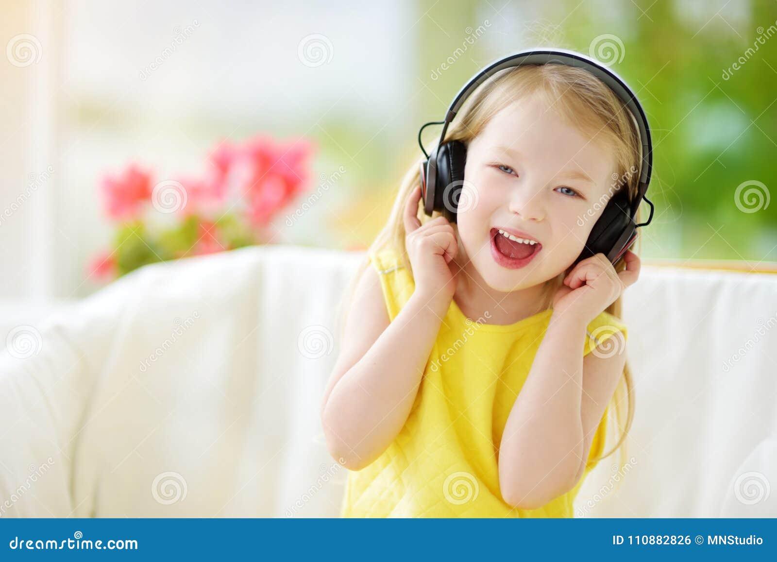 Милая маленькая девочка нося огромные беспроволочные наушники Милый ребенок слушая к музыке Школьница имея потеху слушая к ` s ре