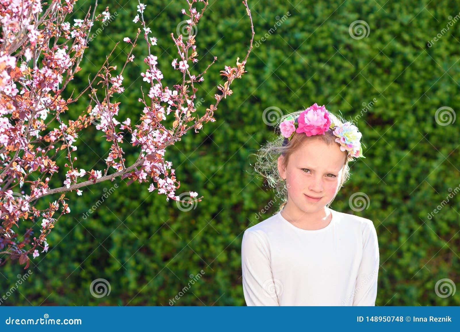 Милая маленькая девочка представляя со свежими фруктами в солнечном саде